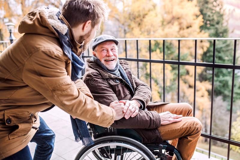 Senior father in wheelchair and young son on a walk. royalty free stock image
