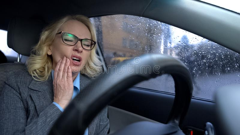 Senior female in business suit feeling toothache driving work car, health care stock image