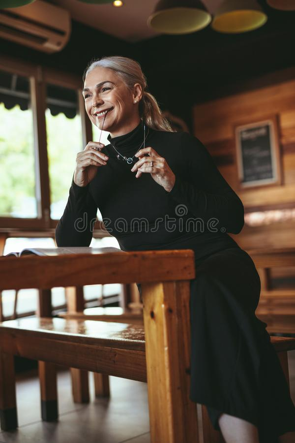 Senior female at cafe looking away and smiling stock images