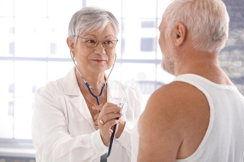 Senior female doctor examining patient royalty free stock image