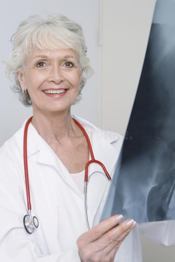 Senior Female Doctor Holding X-ray Report. Portrait of a happy senior female doctor holding the x-ray report in clinic royalty free stock photos