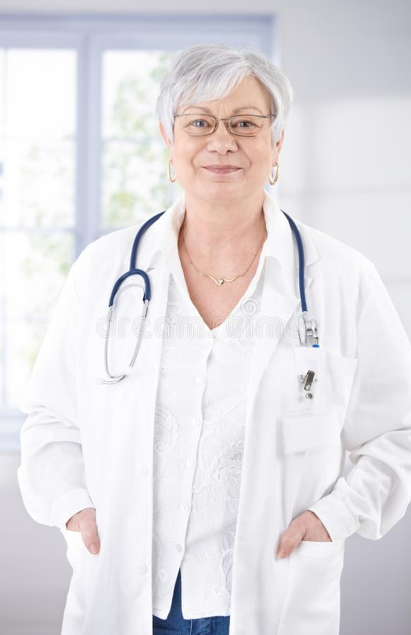 Senior female doctor smiling at hospital corridor stock photos