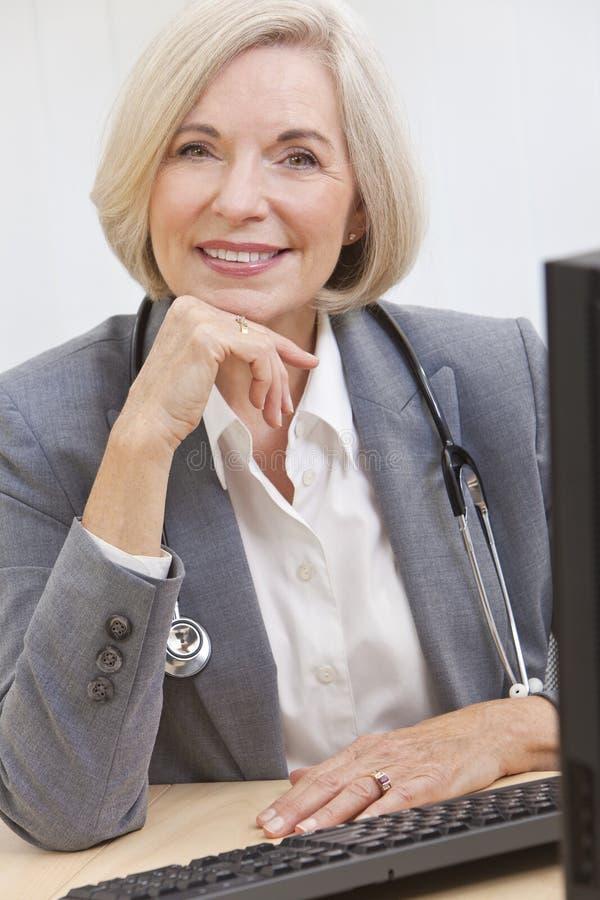 Senior Female Doctor With Stethoscope at Desk stock photo