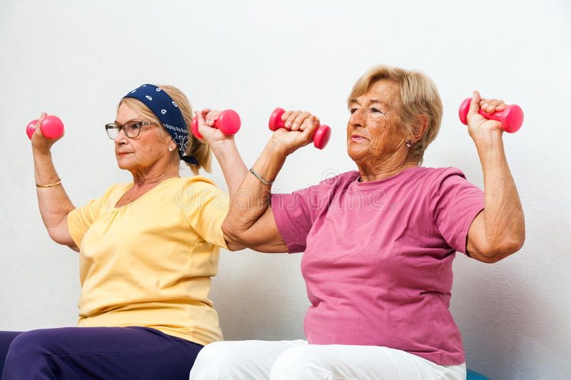 Senior female fitness girls working out with weights. stock image