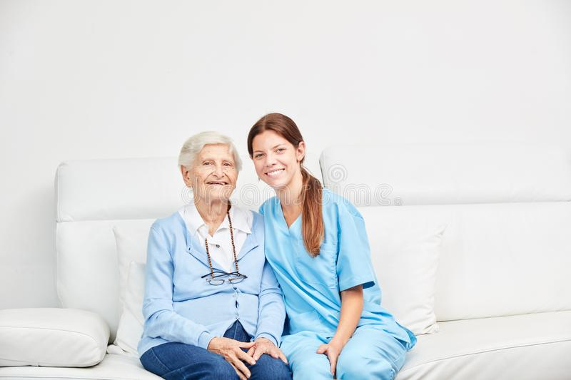 Senior and female geriatric nurse on the sofa. At supervised living royalty free stock photo