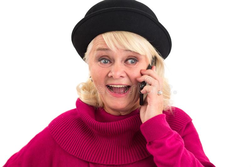 Senior female holding cellphone. Woman talking on the phone. I have news for you stock photography