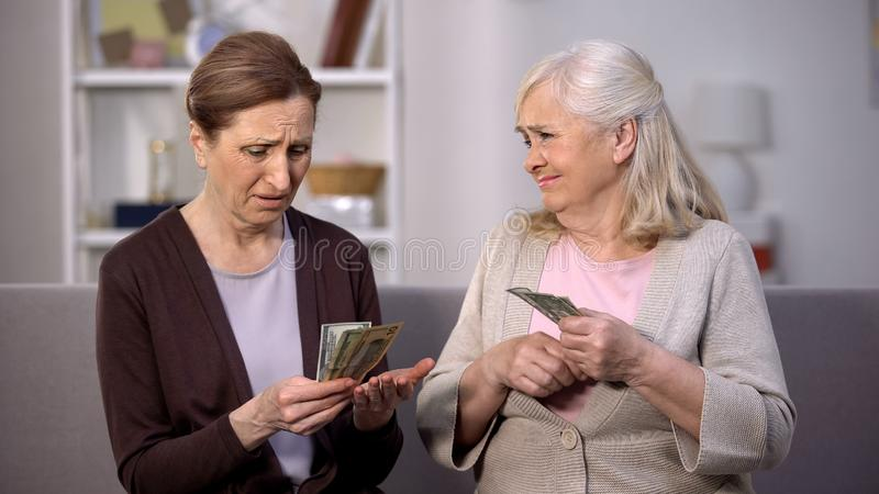 Senior female holding dollars complaining friend on poverty problem, low income. Stock photo stock photos