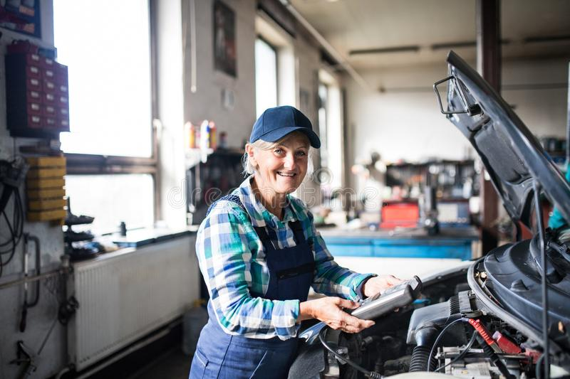 Download Senior Female Mechanic Repairing A Car In A Garage. Stock Image - Image of professional, occupation: 110840647