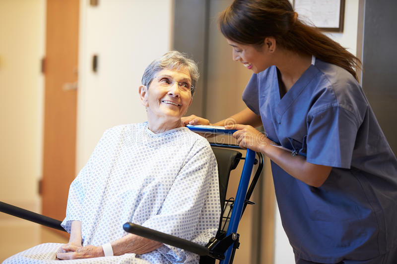 Senior Female Patient Being Pushed In Wheelchair By Nurse stock image