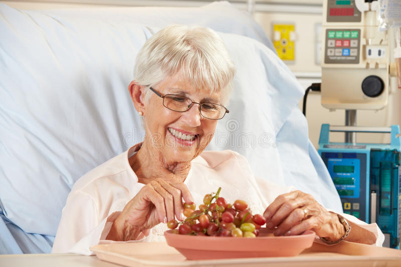Senior Female Patient Eating Grapes In Hospital Bed stock photos