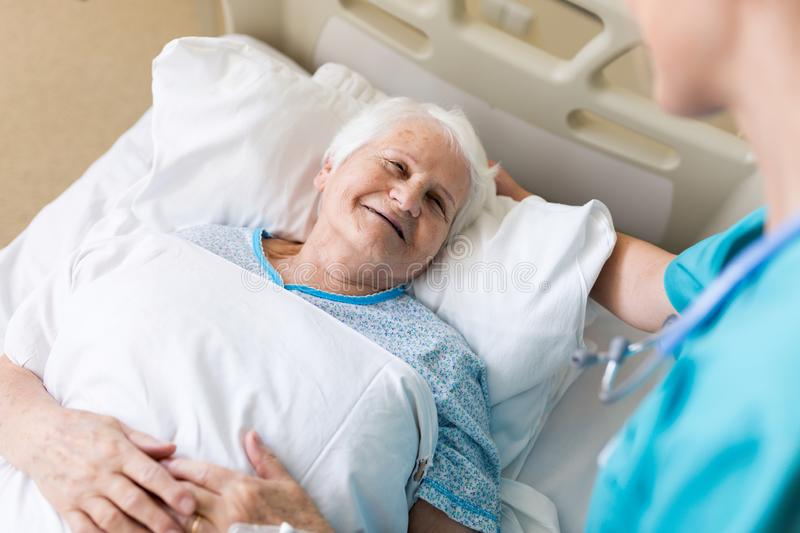 Senior female patient in hospital bed stock images