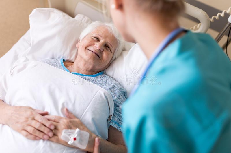 Senior female patient in hospital bed stock image