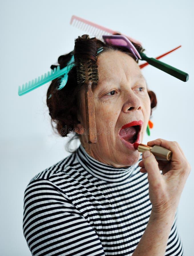 Senior female putting lipstick royalty free stock image