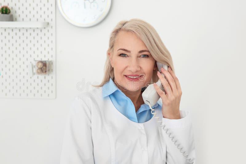 Senior female receptionist working stock images