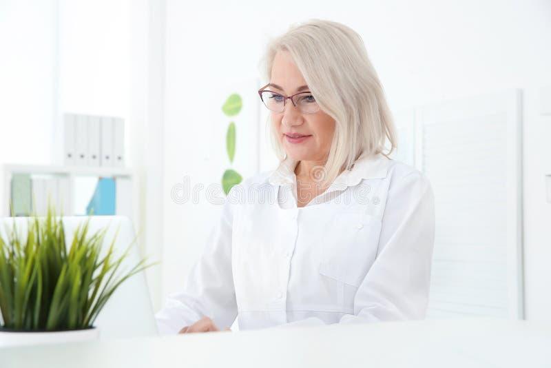 Senior female receptionist working. In hospital stock photo