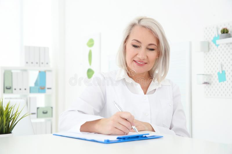 Senior female receptionist working. In hospital royalty free stock photography