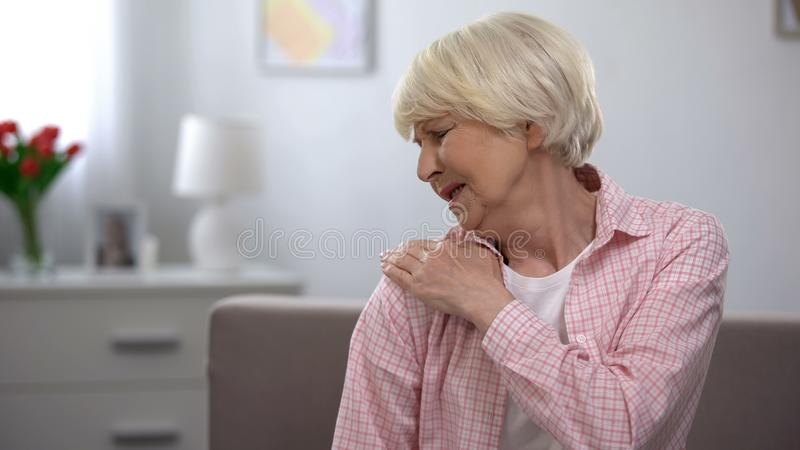 Senior female suffering from pain massaging shoulder, joint disease, arthritis. Stock photo royalty free stock photography