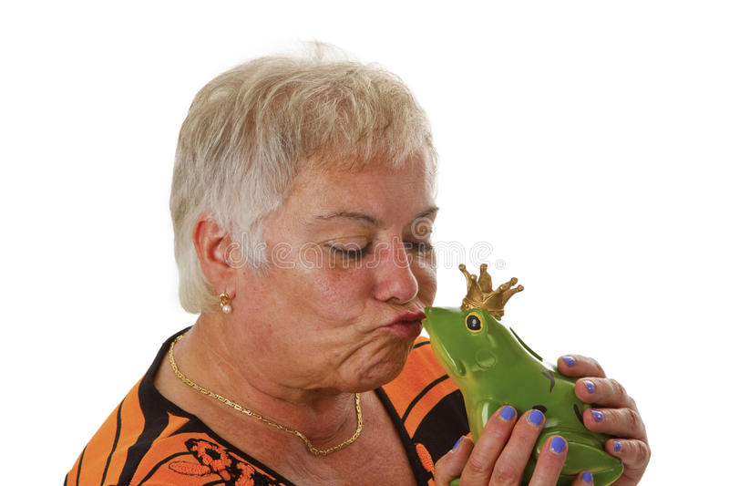 Senior female with a toy frog prince. Isolated on white background stock photography