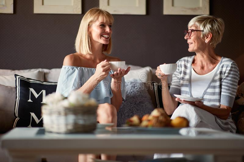Senior female with young woman drinking coffee stock photo