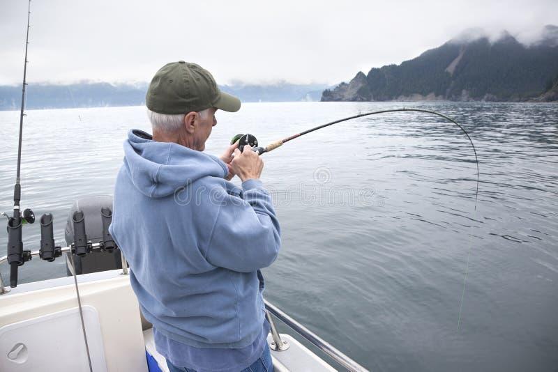 Senior fisherman reeling in a fish near Seward, Alaska stock photography