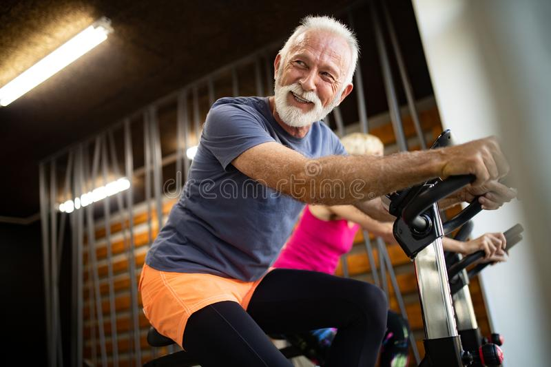 Mature fit couple exercising in gym to stay healthy. Senior fit couple exercising in gym to stay healthy stock photo