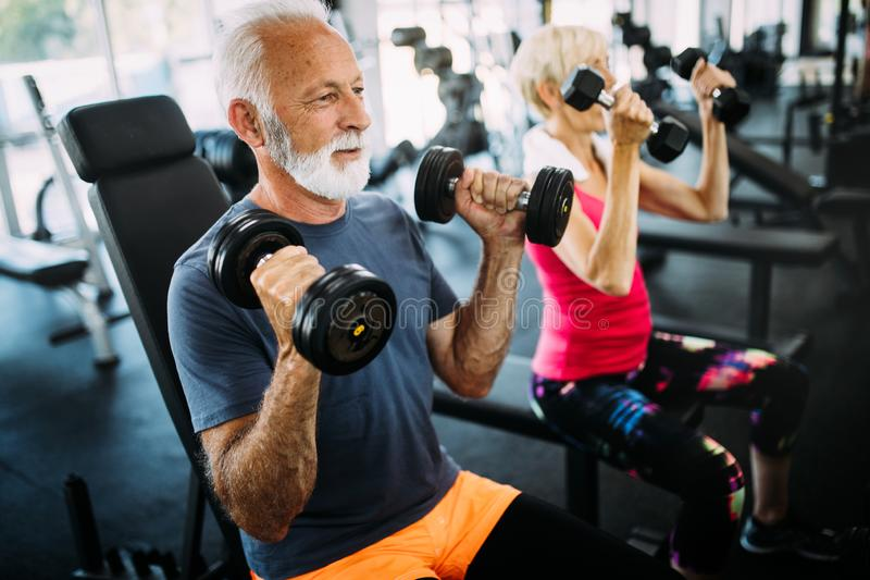 Senior fit man and woman doing exercises in gym to stay healthy royalty free stock images