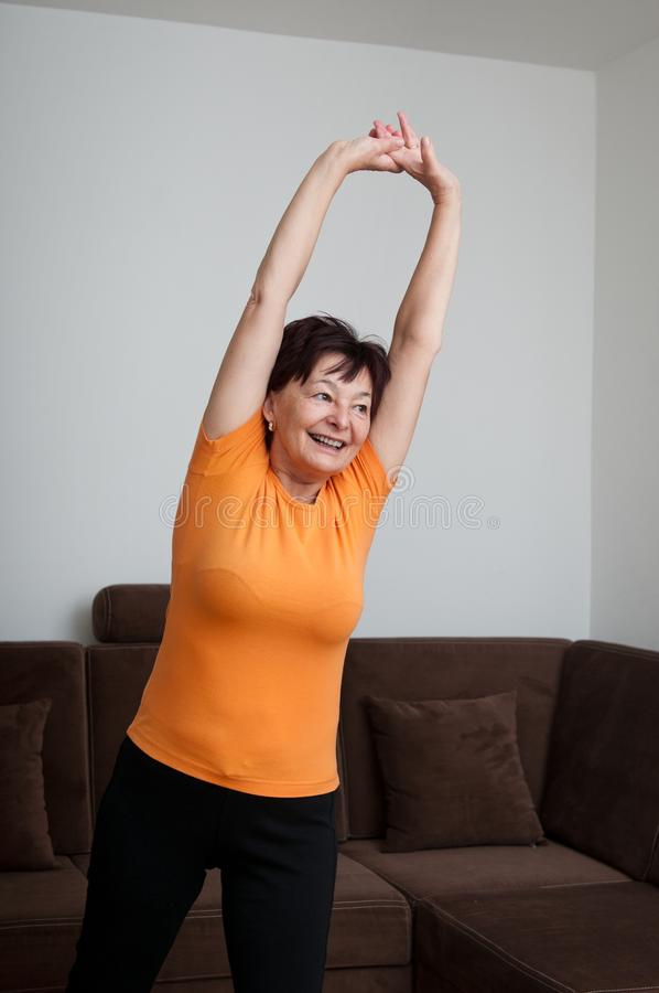 Senior fitness woman exercising at home stock photography