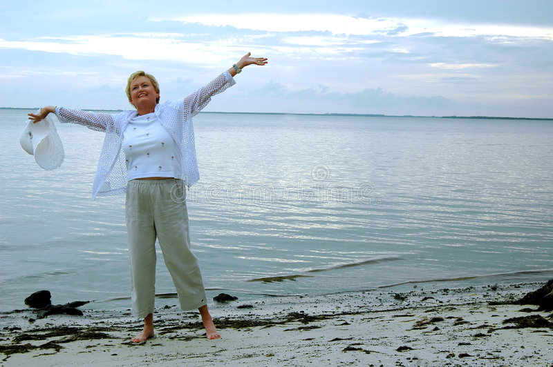 Senior freedom/praise. A senior woman on the beach with arms stretched out to sky stock images