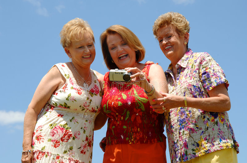 Senior friends checking photo. Three senior women outside checking the screeen of a digital camera during a vacation photo together royalty free stock images