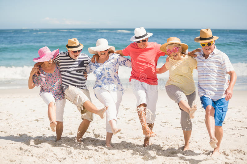 Senior friends dancing on the beach royalty free stock photography