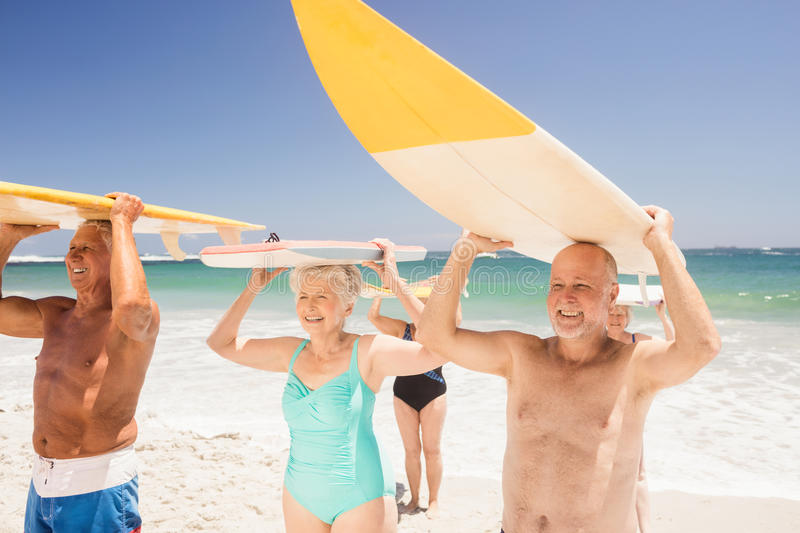 Senior friends holding surfboard royalty free stock photography