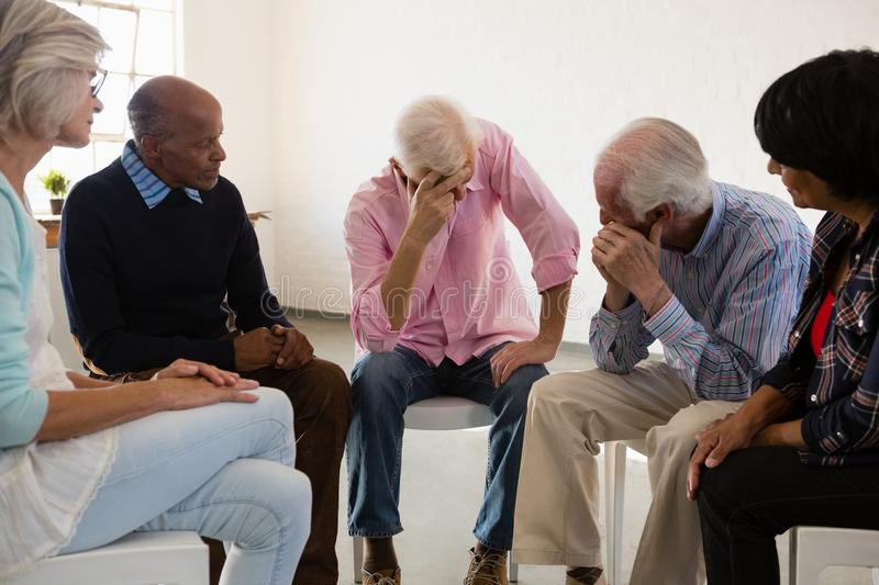 Senior friends looking at man with head in hand royalty free stock image