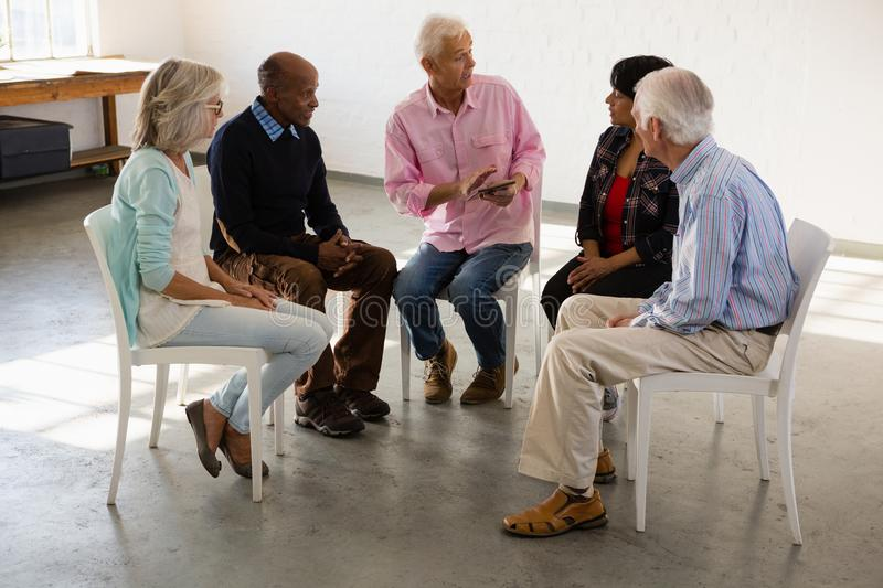 Senior friends looking man talking while sitting on chair stock photography