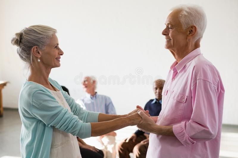 Senior friends looking at man and woman holding hands stock photos