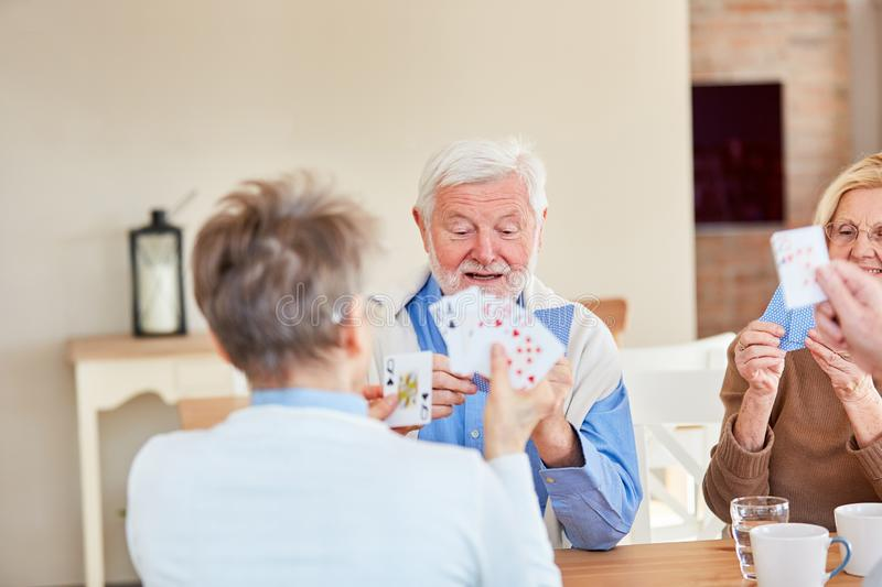 Senior friends play cards in the retirement home. Senior friends playing cards together in the retirement home royalty free stock images