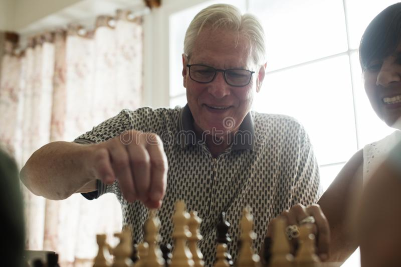 Senior friends playing chess together stock photography