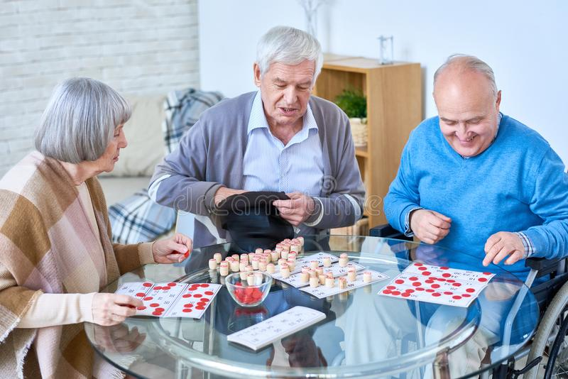 Senior Friends Playing Lotto in retirement Home. Portrait of senior people playing lotto game sitting at glass table in living room of retirement home stock photography