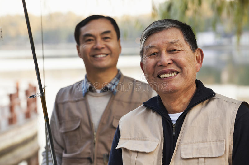 Senior friends portrait while fishing at a lake stock images