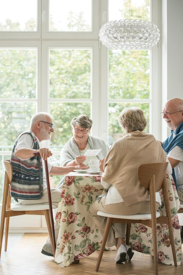 Senior friends spending time together by drinking tea and enjoying photos stock photography