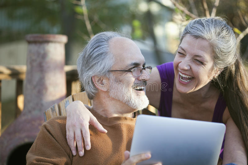 Senior fun with a tablet PC. Mature couple laughing while sharing a digital tablet stock photography
