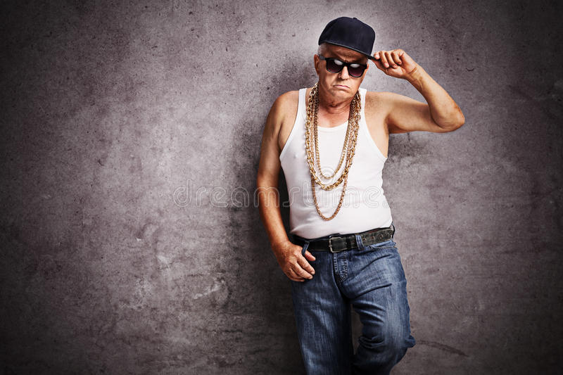 Senior gangster in baggy hip-hop clothes. Looking at the camera and leaning against a rusty gray wall royalty free stock photos