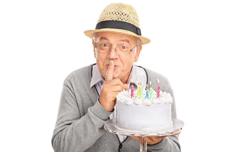 Senior gentleman carrying a birthday cake. And holding a finger on his lips isolated on white background stock image