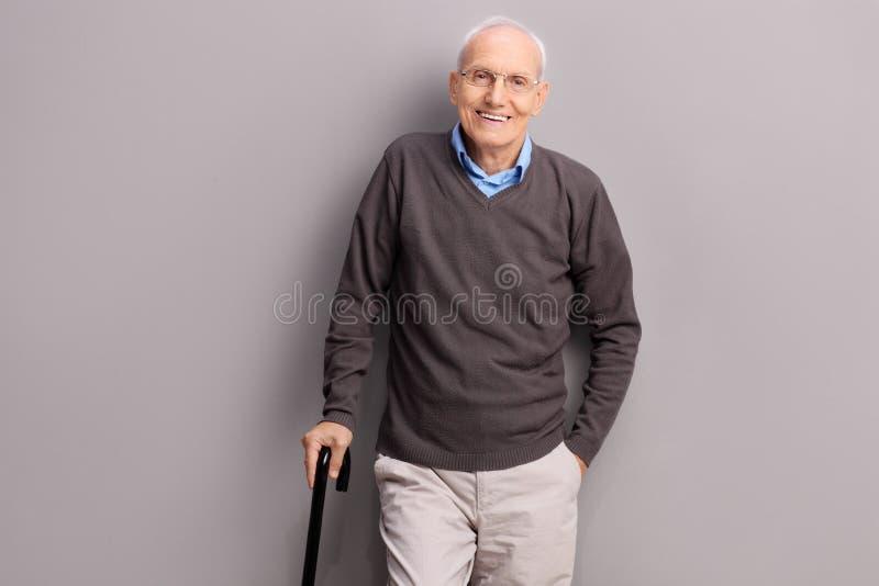 Senior gentleman holding a black cane royalty free stock photo