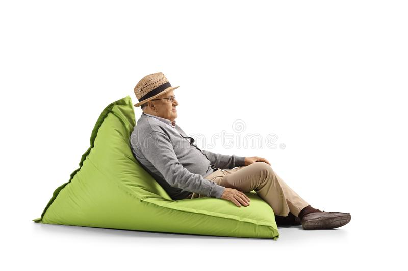 Senior gentleman resting on a bean-bag chair. Full length shot of a senior gentleman resting on a bean-bag chair isolated on white background royalty free stock images