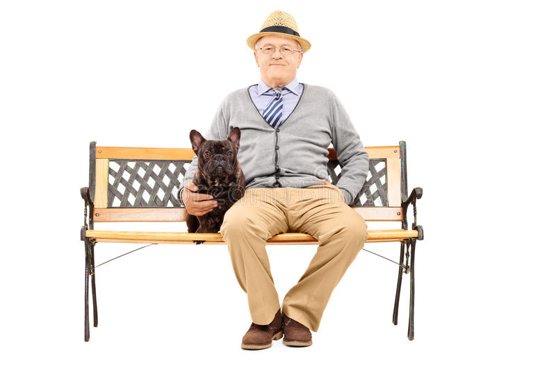 Senior gentleman seated on a bench with his dog royalty free stock photography