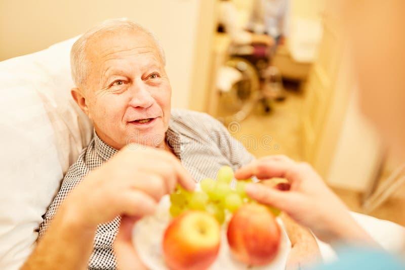 Senior gets fresh fruit in retirement home. Senior gets fresh fruit from a nursing assistant in retirement home or at home royalty free stock photo