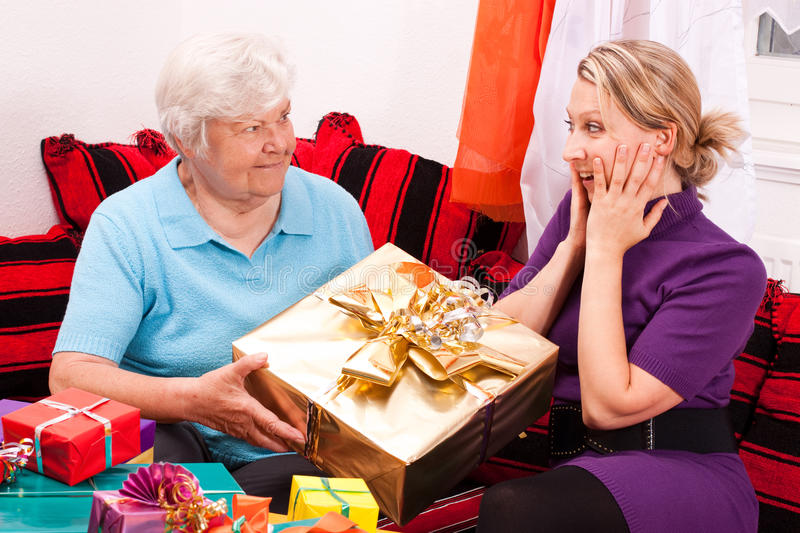 Senior gives gift to young pretty woman. Female senior gives present to young blond woman stock photos