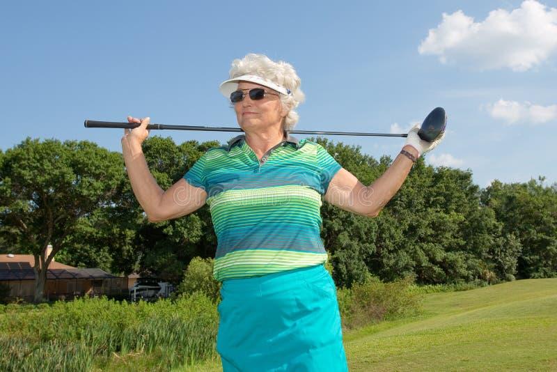 Senior Golfer. Senior female golfer standing on a golf course in a retirement community royalty free stock photo