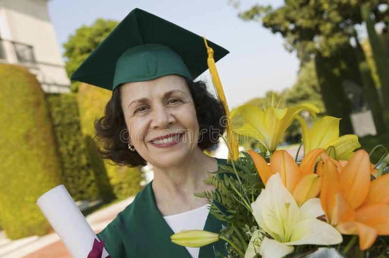 Senior Graduate holding diploma and flowers royalty free stock photo