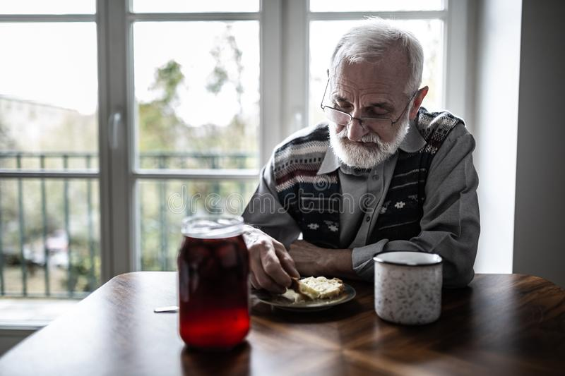 Senior grandfather with grey hair and beard sitting alone in the kitchen eating breakfast royalty free stock photos